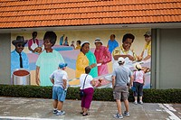 People looking at art murals painted on outdoor building walls in Lake Placid Florida known as the Town of Murals.