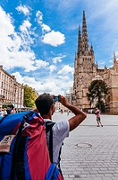 Young man taking photos of the Saint André Cathedral, Bordeaux, France.