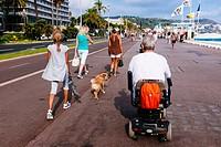 Tourists walking on Promenade des Anglais. Nice, Alpes-Maritimes, French Riviera, Provence-Alpes-Côte d´Azur, France.