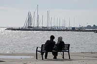 A couple sits on a bench by the sea on a blustery day.