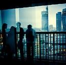 dos parejas hombre mujer irreconocibles mirando la City desde el mirador un atardecer vistos a traves de del cristal de un ventanal . Tate Modern, The...