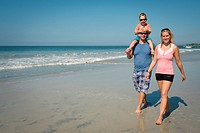 Family of 3 enjoying walk on the beach, Riviera Nayarit, Mexico.