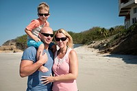 Family of 3 on the a beach, father - mother - toddler child.
