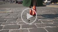 Sexy woman legs walking on cobblestone street