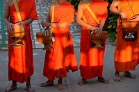 Buddhist monks walking along road to collect alms, Four Thousand island,South Laos,Southeast Asia.
