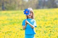 Boy with Pinwheel in a Meadow of Dandelions.