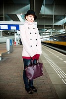 Tilburg, Netherlands. Young adult fashionable woman commuting by train towards an assignment as music teacher.