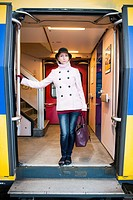 Breda, Netherlands. Young adult woman waiting inside the door of her intercity train for departure to her work assignment as a music teacher.