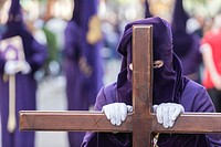 Penitent dressed in purple tunic of velvet resting on wooden cross during atonement station on Holy Week, Andalusia, Spain.
