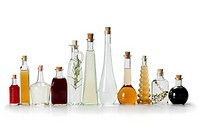 Row of bottles with homemade organic vinegar on white background.