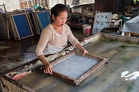 The jute paper production (fibers are being spread in water in a sift) in Ban Xang Khong, a village near Luang Prabang in Central Laos, which is known...