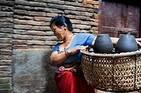 Local woman transport pots to dry in the sun, Pottery Square, Bhaktapur, Nepal.