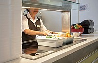 Canteen assistant preparing and serving food in a hospital