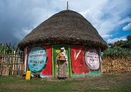 Ethiopian woman standing in front of her traditional painted house, Kembata, Alaba Kuito, Ethiopia.
