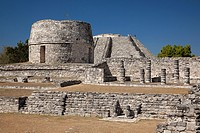 View to the Templo Redondo-Round Temple and to the visitors climbing up to the Castle of Kukulcan-Castillo de Kukulcan in the background in Mayapan Ar...