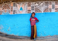 Ethiopian girl standing in front of her traditional painted house, Kembata, Alaba Kuito, Ethiopia.