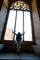 Tourist with the sign of victory in one of the windows of the Long of the Silk, Valencia, Spain