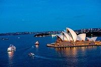 Sydney Harbour at dusk with boats and opera house.