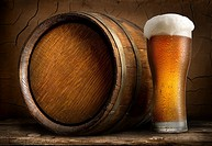 Beer in cask and glass on wooden table.