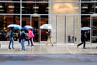 New York City, Manhattan. Rainy Day. People Holding Umbrellas, Walking Past an Office Building Entrance.
