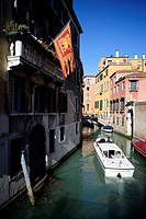 Italy, Veneto, Venice, listed as World Heritage by UNESCO, boat on a canal and venetian flag