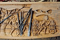 Ornate details on a wood table in a furniture workshop( Bastar region, India). The sculpture is representing tribal people.