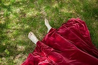 Close-up of a young woman's feet sticking out from under her long red vintage dress.