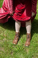 Young woman's legs wearing boots and a long red vintage dress.