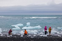 Tourists looking at the ice chunks floating out of the Jokulsarlon glacier lagoon in Iceland.