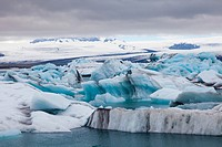 Icebergs floating in the Jokulsarlon glacial lagoon in Iceland under an overcast sky.