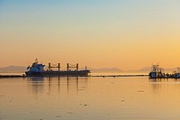 Freighter leaving the Fraser River at sunset, near Vancouver, British Columbia, Canada