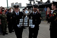 Two male officers happily carry the Memorial Cup trophy from a ship past a crowd of spectators and an honour guard.