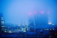 Vista parcial de la ciudad con edificios de viviendas y oficinas en primer plano al atardecer con niebla y las luces encendidas. Londres, Bankside, Ta...