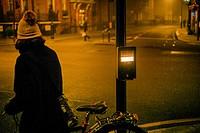 Mujer de espaldas irreconocible con una bicicleta de noche en un paso cebra con el signo ´WAIT´ London, UK, Europa.