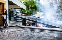 Grill heating up ready to start cooking. Outdoors restaurant.