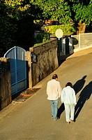couple walking, Rue Taillefer, Lauzun, Lot-et-Garonne Department, New Aquitaine, France.