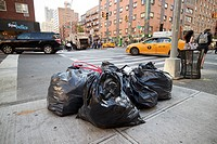 garbage left on sidewalk in black plastic bags for collection new york streets USA.