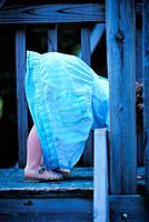 Little girl in blue denim dress bending over