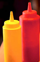 Vertical shot of yellow and red plastic mustard and ketchup dispensers