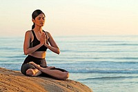Indian girl meditating on beach in Carlsbad. California, USA