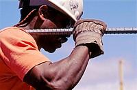 Ironworker carrying long rebar. I-880 Cypress project. Oaklnad, California. USA.