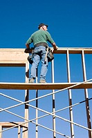 Carpenter standing on scaffolding looking over the top of second story wall at a construction site.