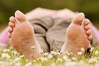 Close-up of undersides of bare feet of woman lying on grass.