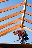 Carpenter hammering trimmer to center post while standing below the framing of the roof rafters at a construction site.