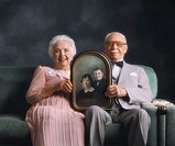 Elderly couple holding photo from when they were just married.