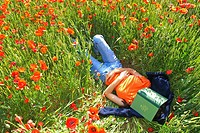 Woman lying on a poppies field