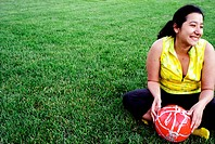 Latino woman holding soccer ball - football