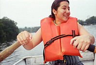 Latino woman rowing boat.