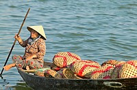 Woman in boat near fish market in Hoi An, Vietnam.