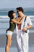 couple sightseeing and embracing on beach